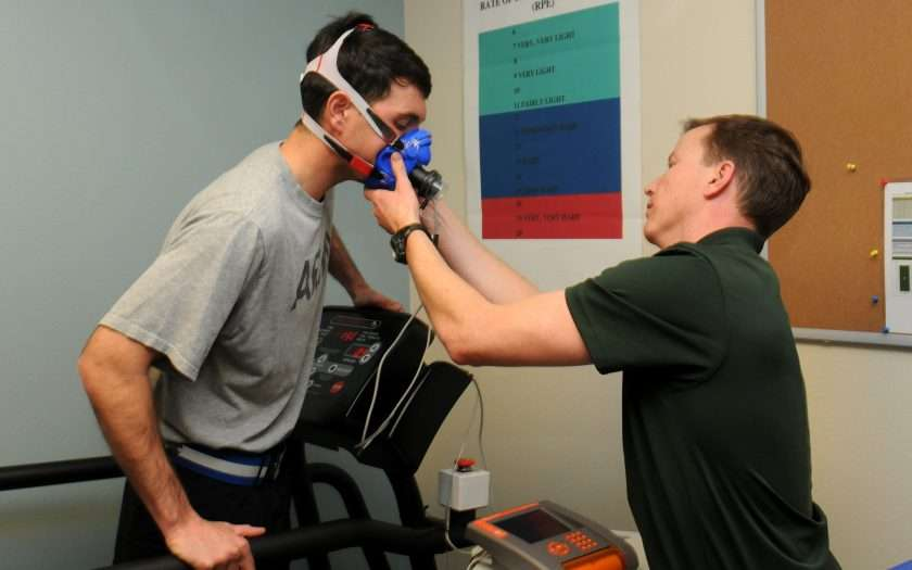 Person standing on a treadmill with oxygen mask on his face.