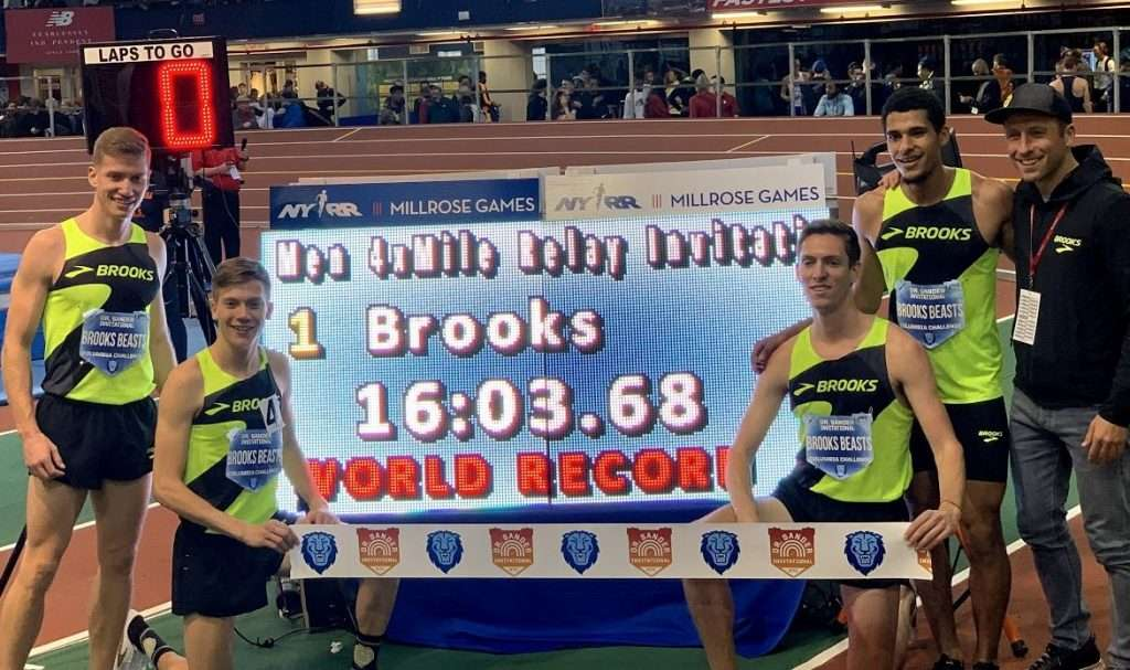Brooks Beasts Team poses in front of sign displaying their new 4 x mile world best