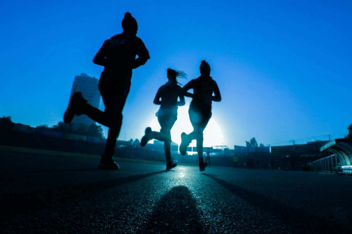 Silhouette of three runners