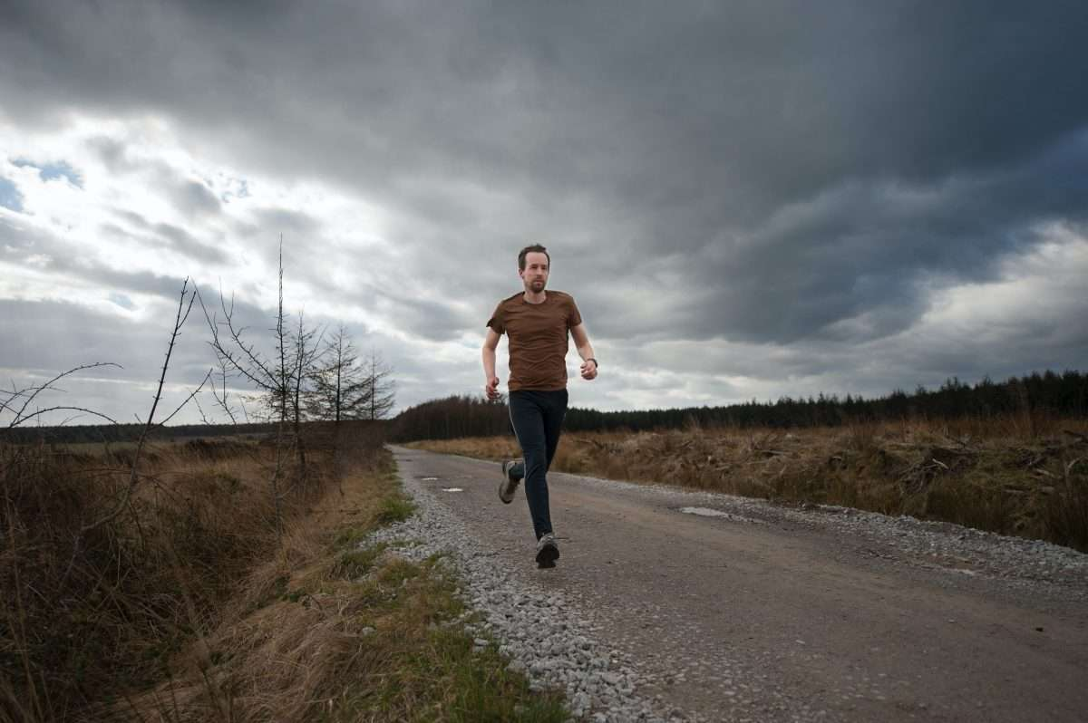 Man running under clouds on gravel road